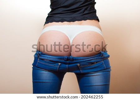 close up image of sexy hot loins in white lace underwear. slim fitness beautiful young woman standing in jeans having fun posing showing her excellent shape buttocks on light copy space background - stock photo