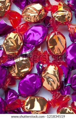 Close-up image of shiny golden and purple hard candies randomly arranged over white. - stock photo