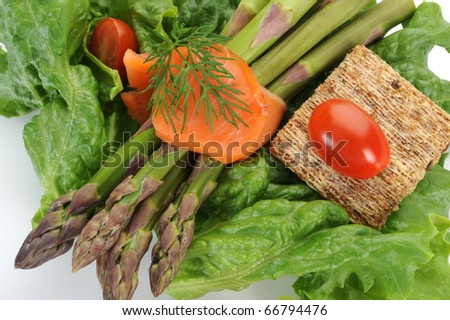 Close-up image of smoked salmon served with asparagus and salad