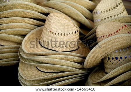 Close up image of stacks of straw cowboy hats - stock photo