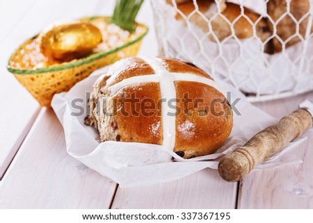 Close up image of tasty Easter cross-bun on white wooden background. Selective focus, shallow depth of field - stock photo