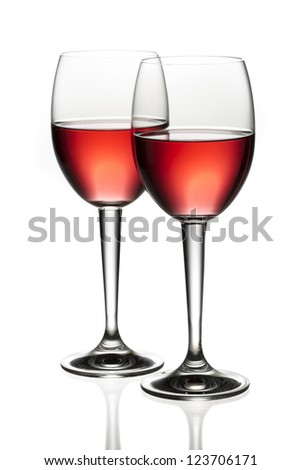 Close-up image of two red wine toasting each other over white background - stock photo