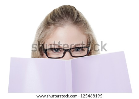 Close-up image of woman covering her face with pink book against the white surface - stock photo