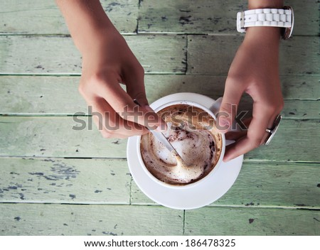 Close up image of woman hands shaking cappuccino at shabby chic table. Morning mood. - stock photo