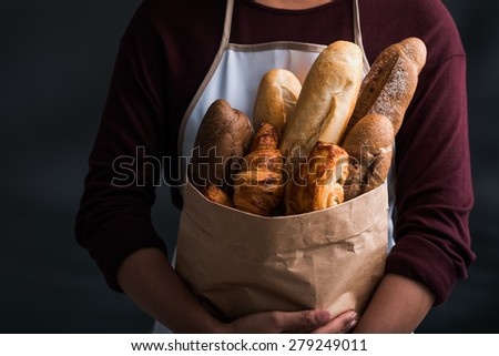 Close-up image of woman holding package of fresh bread - stock photo