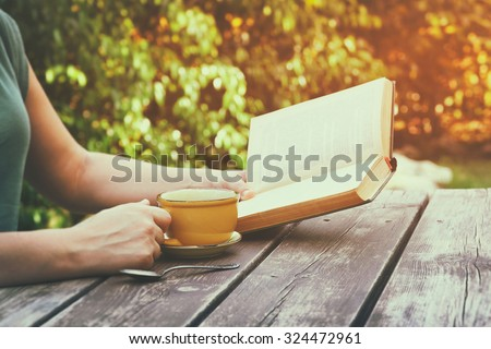 close up image of woman reading book outdoors, next to wooden table and coffe cup at afternoon. filtered image. filtered image. selective focus