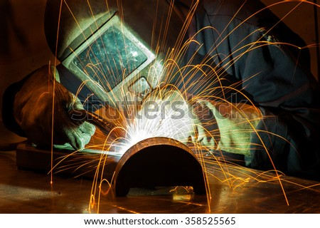 Close-up image of worker with protective mask welding metal