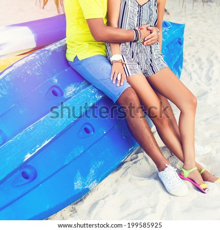 Close up image of young happy couple sitting and hugs at bright blue kayak boat in hot beach, enjoy their vacation and time with each other. Bright sunny colors. - stock photo