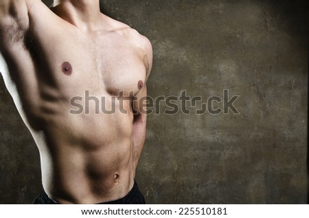 Close up image of young man fitness gym torso with dramatic light on dirty wall background with copy space.