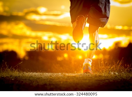 close up image of young man strong legs off trail running at amazing summer sunset in sport and healthy lifestyle concept and jogging cross country training workout - stock photo