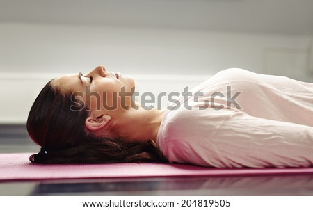 Close up image of young woman lying on a yoga mat with her eyes closed in meditation. - stock photo