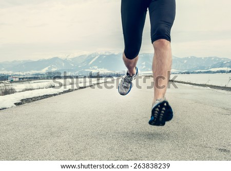 Close up image runner legs on asphalt - stock photo