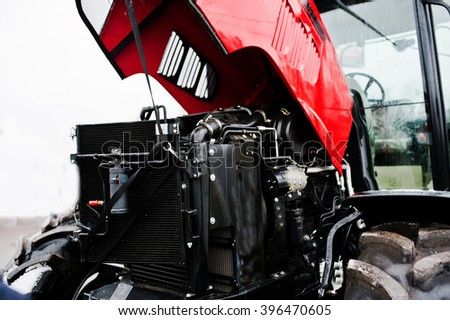 Close up in front of the new red tractor with open motor - stock photo