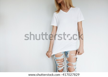 Close up indoor lifestyle portrait of beautiful young blonde woman, standing against white wall, looking away.  Female in blank T-shirt and ripped jeans relaxing at home after hard working day - stock photo