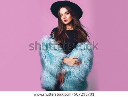 Đóng lên trong nhà chân dung phòng thu thời trang của phụ nữ tuyệt đẹp trong mùa đông phong cách bông áo màu xanh và chiếc mũ màu đen tạo dáng trên nền màu hồng tươi sáng .Spa? E cho văn bản.
