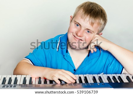 Close up indoor studio portrait of young pianist with down syndrome next to piano keyboard.