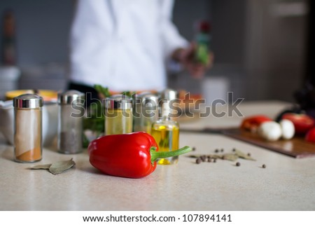 Close-up ingredients  and  a male chef on background  preparing a pizza in a kitchen - stock photo