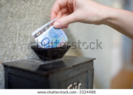 Close-up: Inserting a banknote into offertory box. Very small DOF. - stock photo