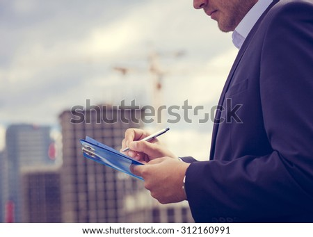 Close-up inspector  holding clipboard on the background of construction