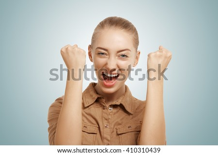 Close up isolated portrait of ecstatic Caucasian young female screaming and holding fists in winning gesture. Studio shot of successful woman winner with happy and celebrating victory expression - stock photo