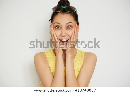 Close up isolated portrait of pretty woman with dark hair and brown eyes wearing yellow top looking in shock at the camera while posing against white blank studio background. Human face expressions  - stock photo