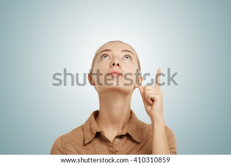 Close-up isolated portrait of smiling beautiful woman looking and pointing up with hopeful and dreamy expression. Studio shot of young Caucasian blonde female posing against blank blue space.  - stock photo
