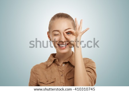 Close up isolated studio portrait of young blonde Caucasian female smiling and looking at the camera through her fingers in okay gesture. Human face expressions and emotions, body language  - stock photo