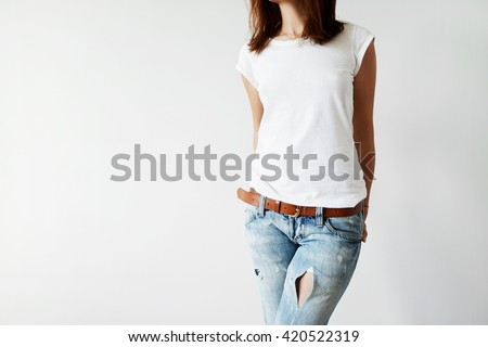 Close up isolated view of young female with dark hair in white T-shirt with copy space for your information or advertising content. Woman freelancer in casual clothes holding hands behind her back   - stock photo
