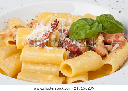 Close-up italian rigatoni plate with prosciutto, parmesan cheese and leaf basil