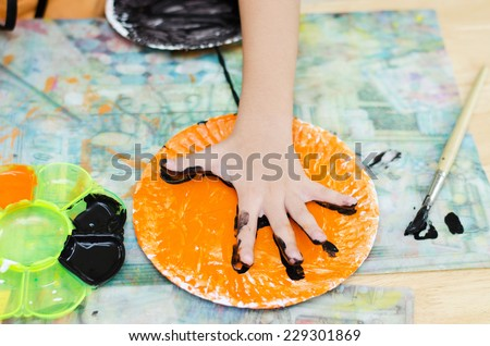 Close up kid hand color painting on paper plate - stock photo