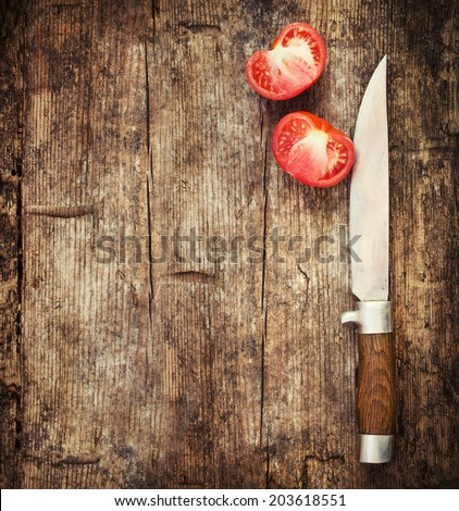 Close up knife and tomato on wooden table - stock photo