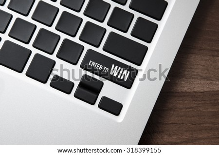 Close up laptop keyboard focus a button with typographic word ENTER TO WIN on table wood. - stock photo