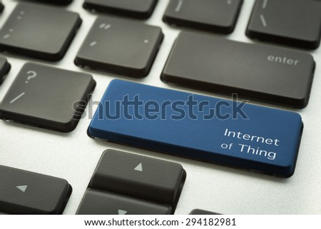 Close up laptop keyboard focus on a blue button with typographic word INTERNET OF THINGS. Technology and computer concepts. - stock photo