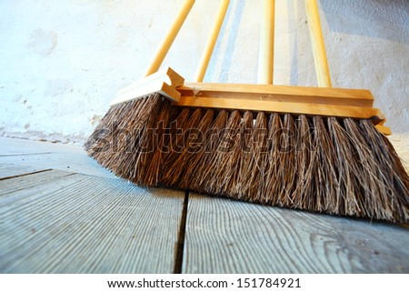Close up large brooms for house work on old wooden floor of country house. Sweeping - stock photo