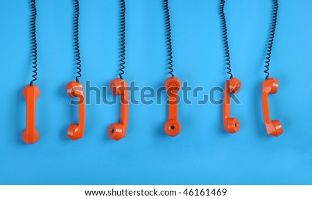 Close-up large group of orange telephones over blue background - stock photo