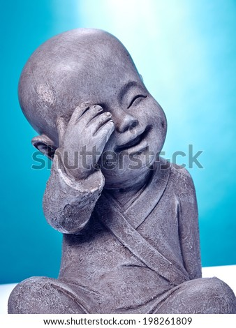 Close Up Laughing Stone Buddah Isolated On Blue Background A young buddah made out of stone, happy expression, laughing about himself. - stock photo