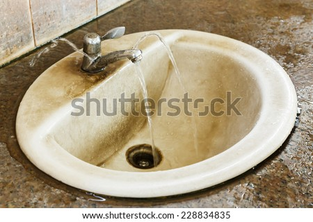 Close up leak and ruin valve in dirty old bathroom - stock photo