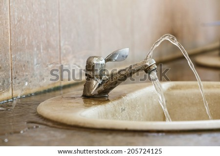 Close up leak and ruin valve in old bathroom - stock photo