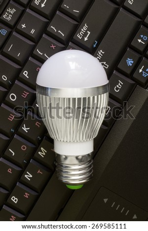 Close up Led Bulb at the keyboard background. - stock photo