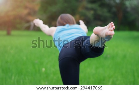 Close-up leg of a young girl who practices yoga in nature. She balances on one leg. Woman covers a ray of sunshine at sunset - stock photo