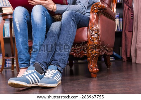 Close up Legs and Feet in Casual Clothing of a Sweet Couple Sitting on One Classic Chair - stock photo