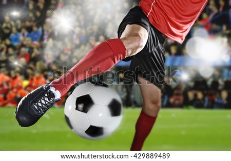 close up legs and soccer shoe of football player in action kicking ball wearing red jersey and sock playing on stadium with audience flashes  and lens flare on the background  - stock photo