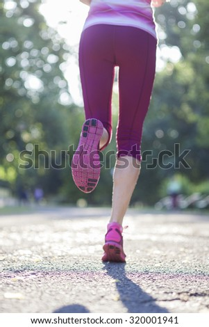 Close-up legs of a girl jogging in the park