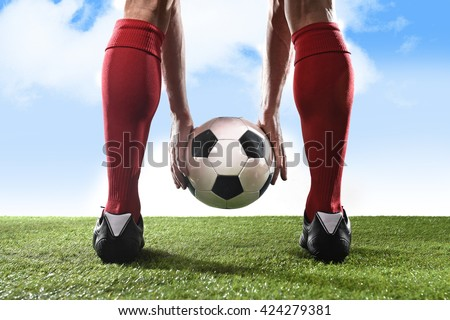 close up legs of football player in red socks and black shoes holding the ball in his hands placing it at the free kick or penalty spot playing outdoors on green grass pitch under a blue sky - stock photo