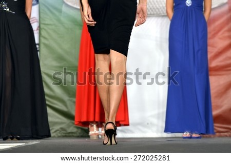 Close up legs of glamour woman in high heels shoes. Fashion young long legs model during a fashion show catwalk in spring time. View from behind. - stock photo