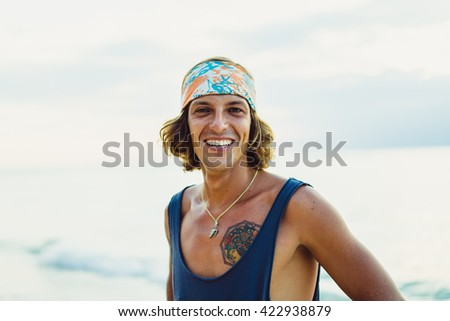 Close-up lifestyle fashion portrait. handsome young man with long curly hair in a bandana smiling.hipster tattoo man.Surfer with a tattoo posing against the backdrop of the ocean. - stock photo