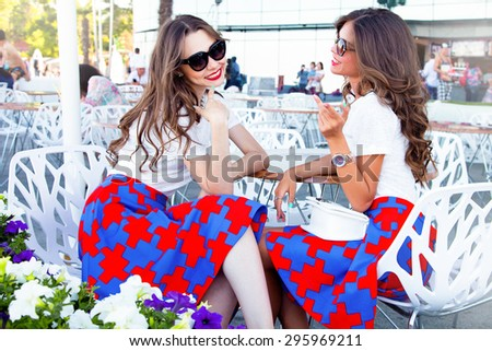Close up lifestyle fashion portrait of two pretty fresh best friends girls,having vacation on street cafe,wearing stylish outfit,sunglasses,bright jewelry,have sexy slim body,fashion bright jewelry. - stock photo