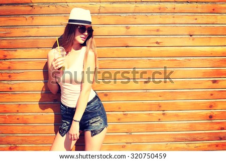Close up lifestyle fashion portrait of woman posing on the street drinking smoothie, wearing stylish outfit and sunglasses, summer hat, joy, relax, vacation. - stock photo