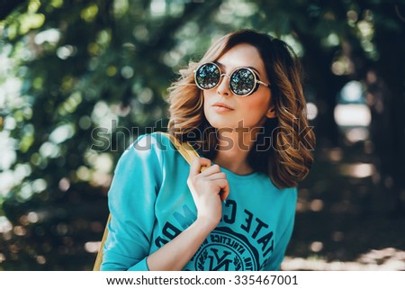 Close-up lifestyle fashion portrait of young hipster woman walking at park , travel with backpack, stylish casual outfit, evening sunset, reflecting sunglasses student, bright make up bf hairstyle - stock photo