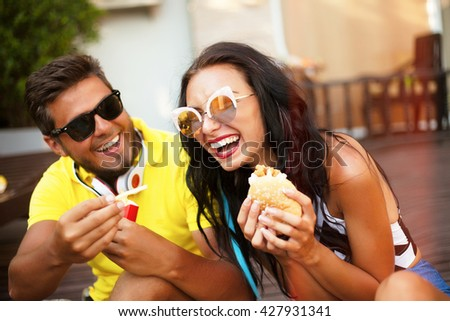 Close up lifestyle funny portrait of couple laughing and having fun together,funny date with burgers and french fry,funny mood and crazy emotions,man joke of her girlfriend,feed her and shows tongue - stock photo